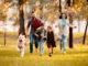 Familienhund rennt mit Familie über die Wiese